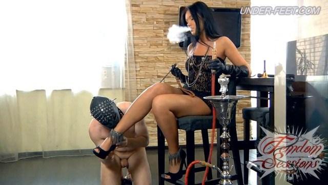 Госпожа курит кальян и топчется каблуками по члену раба, а потом дрочит ногами